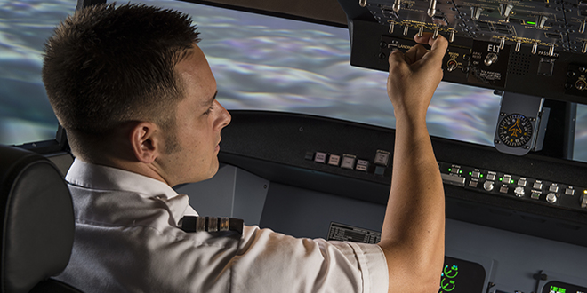 Aviation student in flight simulator turns on guages above him in the plane.