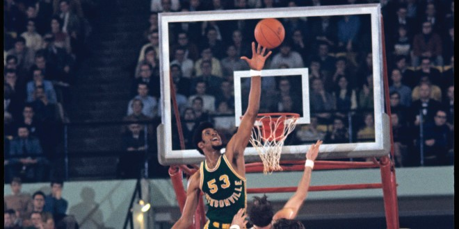 Artis Gilmore reaching for the ball during a game.