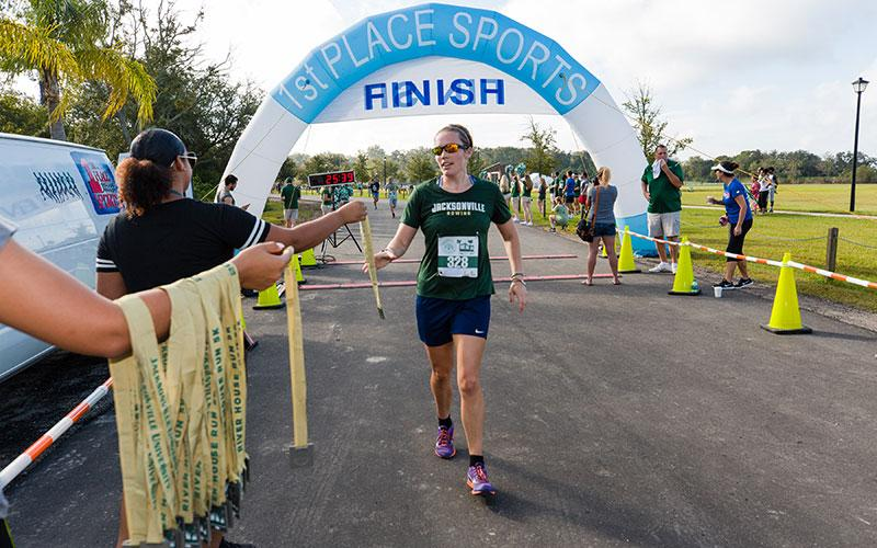 A runner getting her medal after completing the River House Run