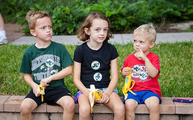 Three children snacking on bananas at the River House