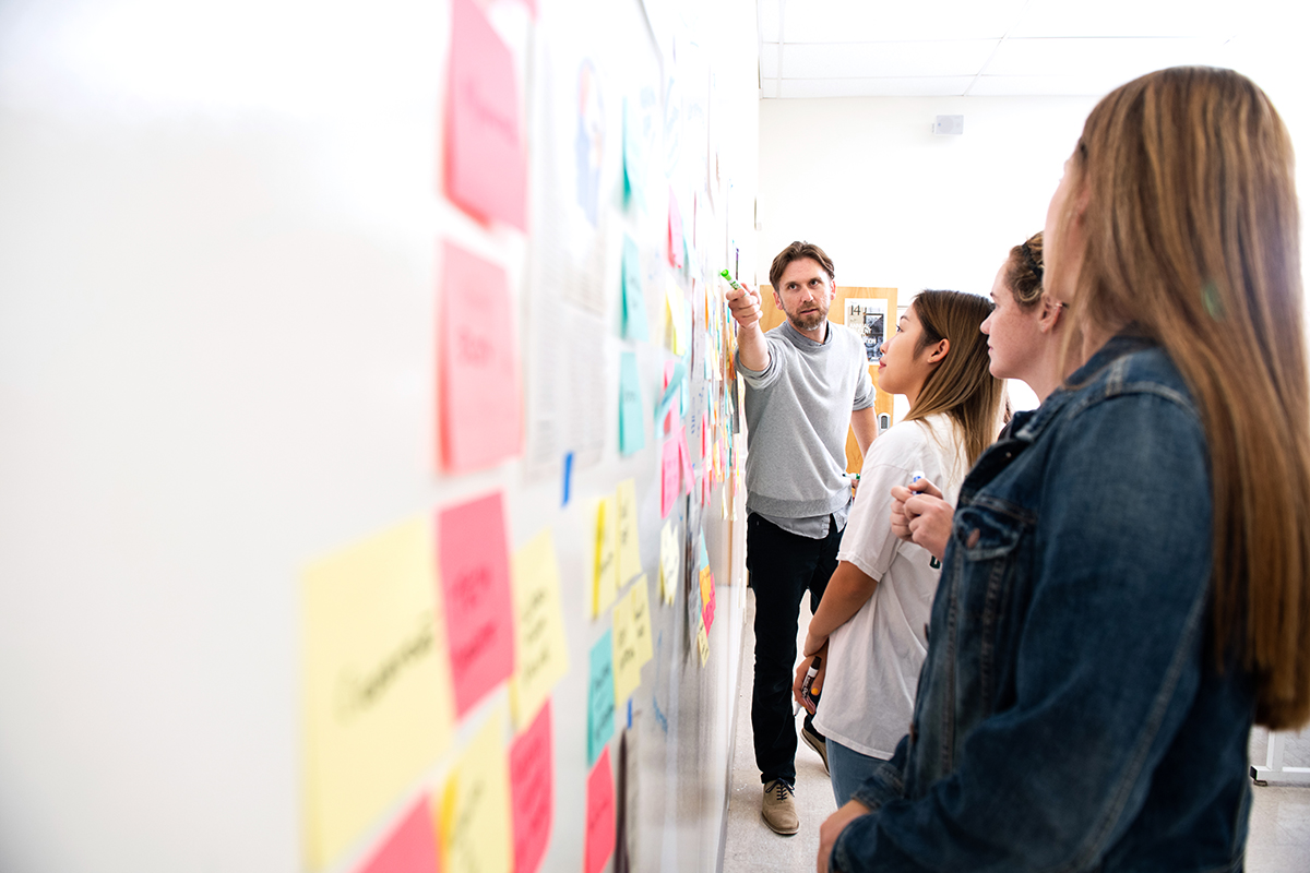 Students and professor engaged in a design thinking exercise using stick notes and collaborating on a writeboard wall.