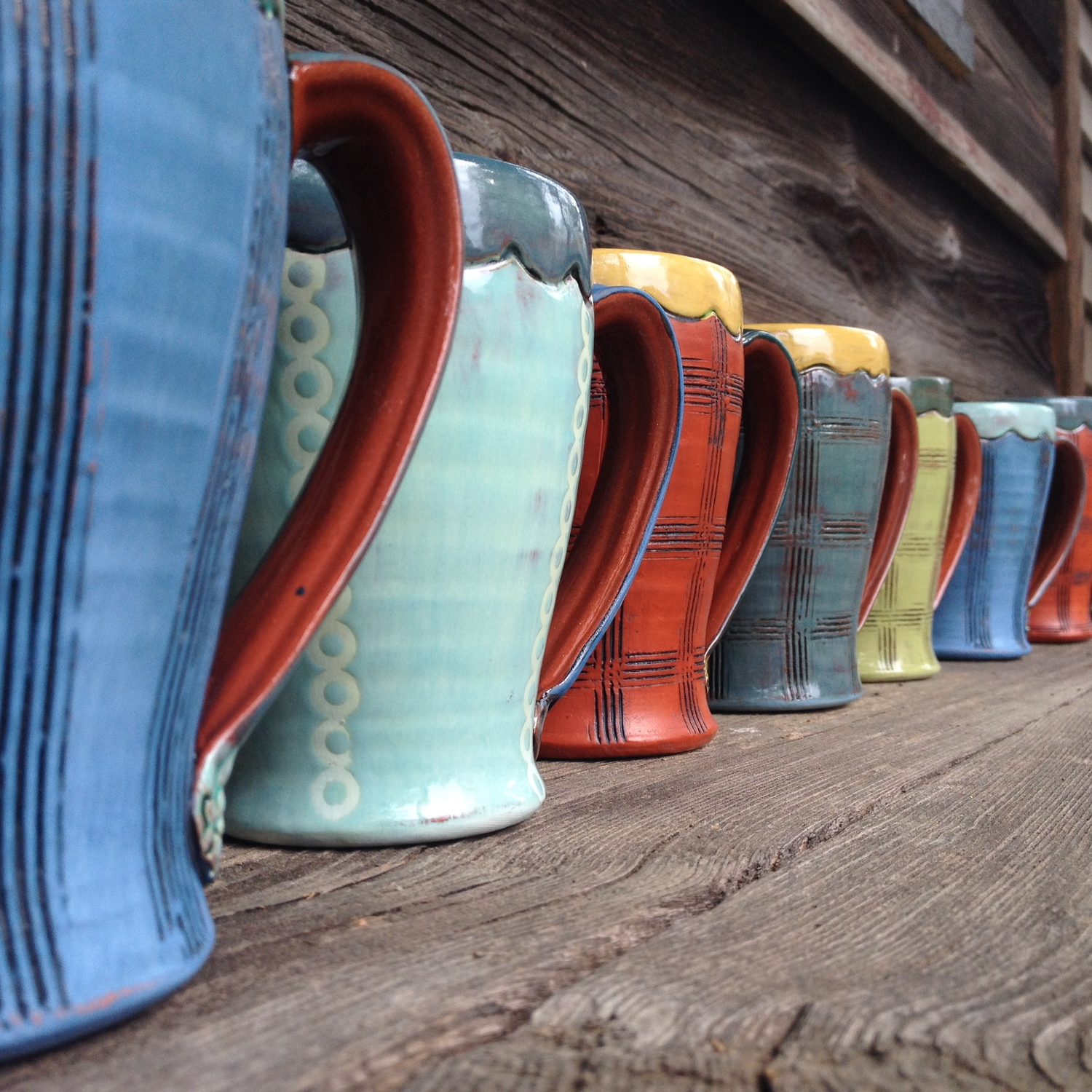 Row of vibrant colored ceramic coffee mugs created by artist Amy Sanders.