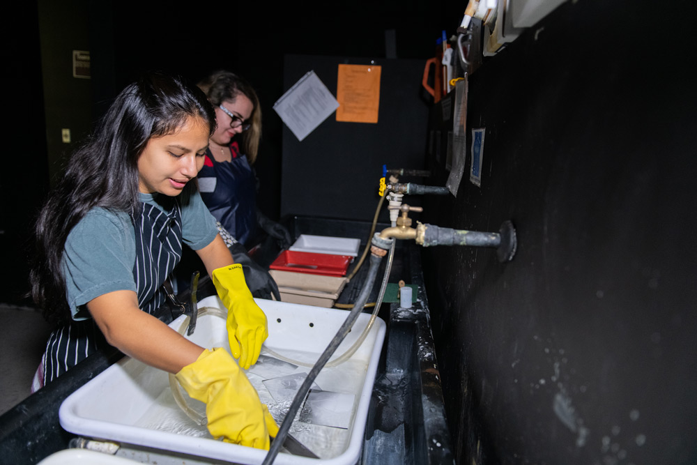 Photography students rinsing prints  in Jacksonville University's Black and White analog darkroom.