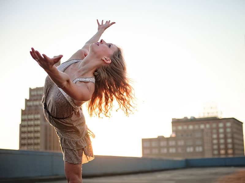 A female soloist dances on a rooftop.