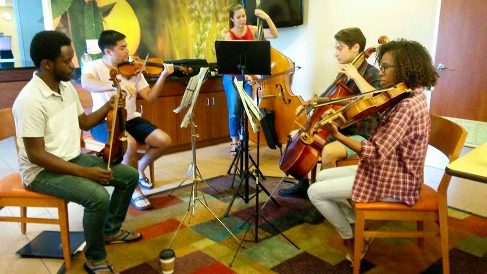 Small group of chamber string performers rehearsing