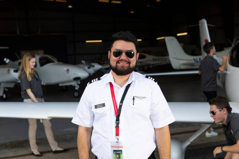 Aviation Pilot smiling in front of a plane hanger.