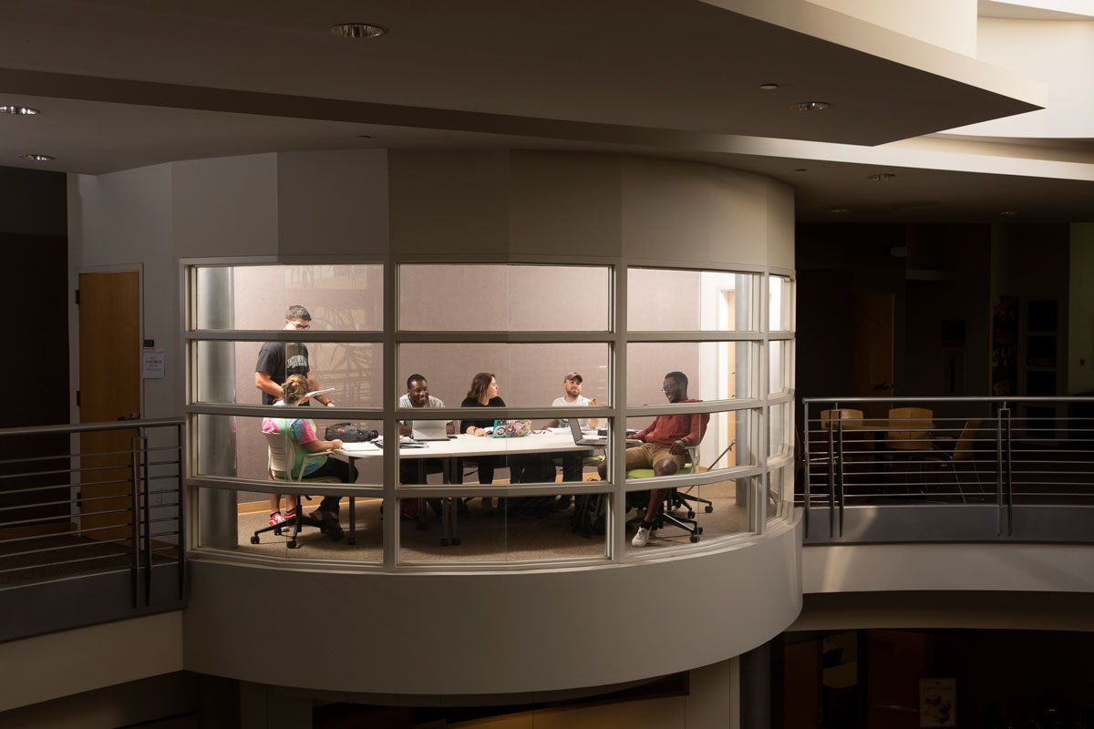Students collaborate in a conference room overlooking the Davis College of Business lobby.