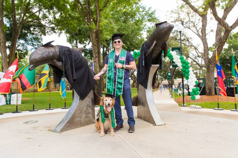 A military veteran standing at the dolphin statue after graduation.