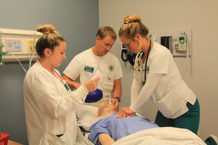 Three nursing students learning in the lab.
